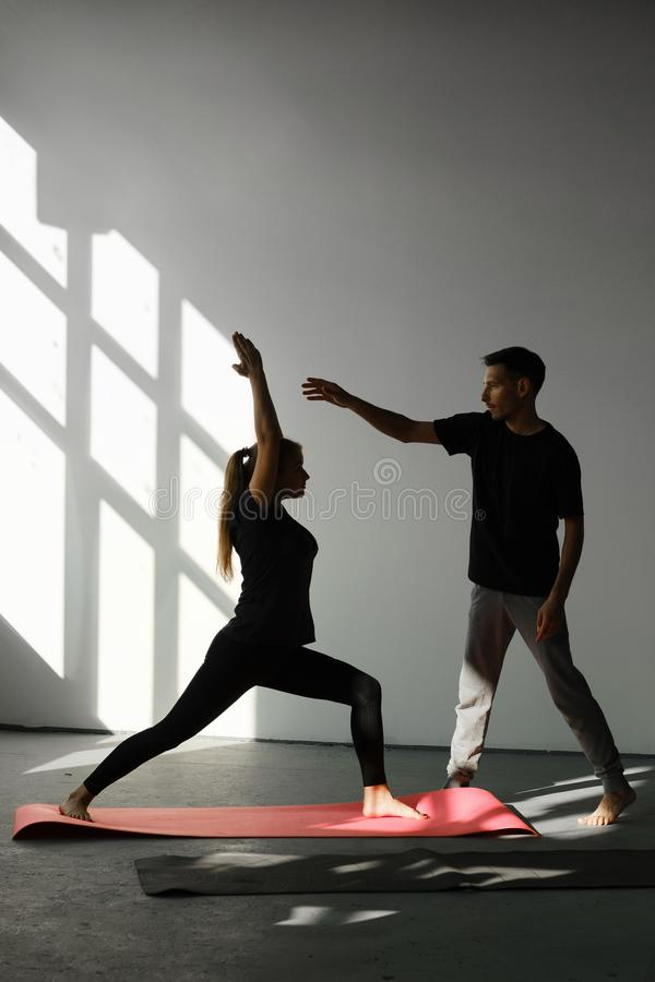 Yoga instructor helps young woman to make exercise rigth. Teacher assists to do yoga pose or asana at seminar. stock photography