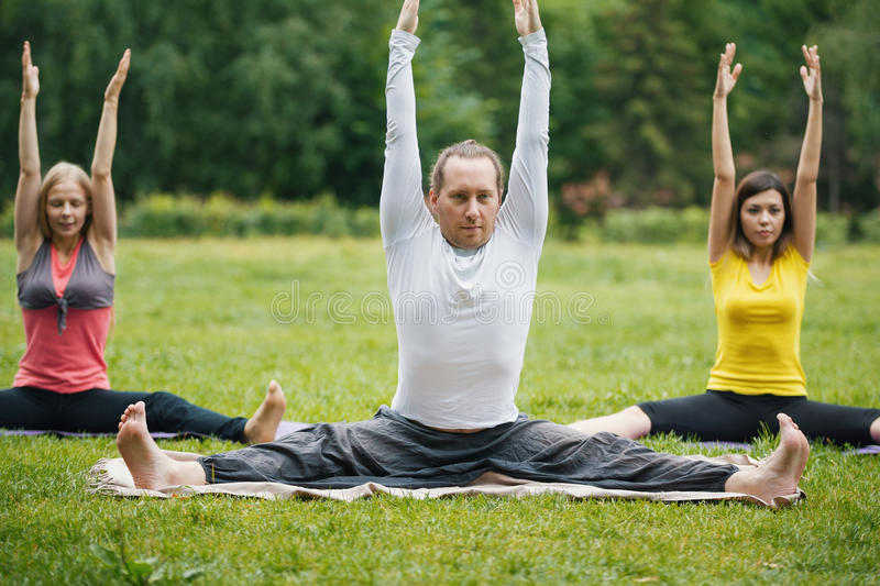 Yoga instructor shows flexibility exercise for group of girls in park. Summer royalty free stock photography