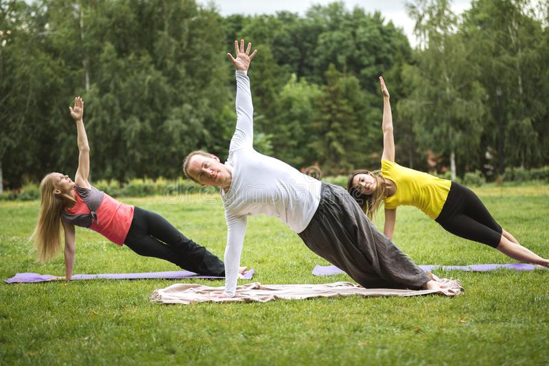 Yoga instructor shows flexibility exercise for group of girls in park. Summer stock image