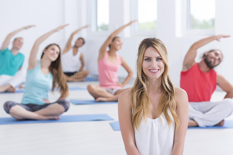 Yoga instructor sitting in front stock images