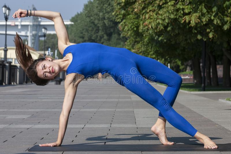 yoga Jovem mulher que faz o exercício da ioga exterior fotografia de stock royalty free