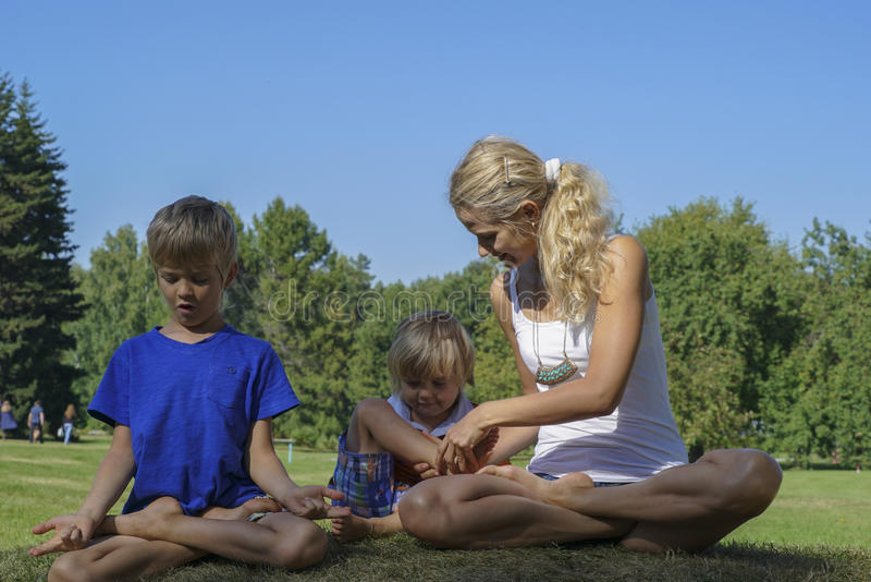 Yoga with kids in the park. Young women helps a child to sit in the lotus position. Yoga with kids in the park stock photos