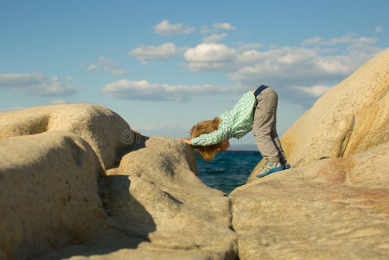 yoga Kinderenyoga Sporten die voor kinderen in aard opleiden Overzees en sport Witte stenen op de kust Leuk jong geitje op overze stock fotografie