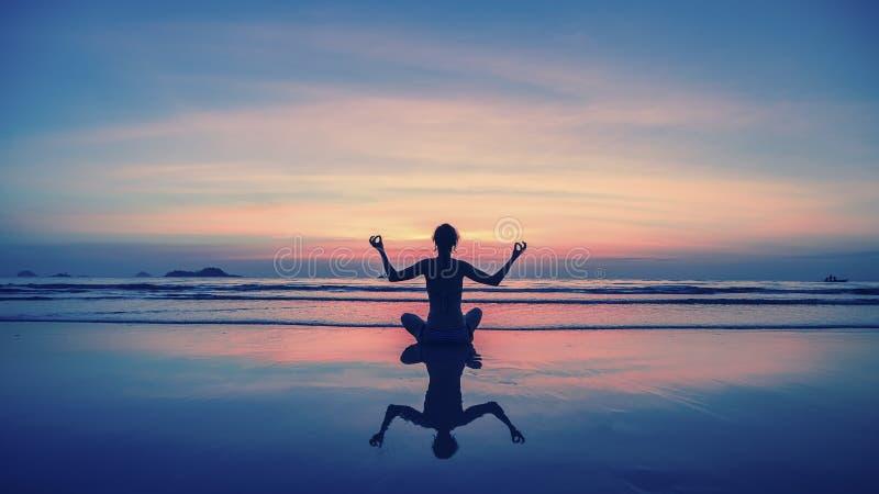 Yoga kondition, sund livsstil Konturmeditationflicka på bakgrunden av det bedöva havet och solnedgången fotografering för bildbyråer