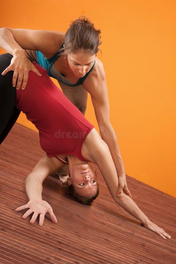 Yoga-Kursleiter, der Kursteilnehmer unterstützt stockfoto