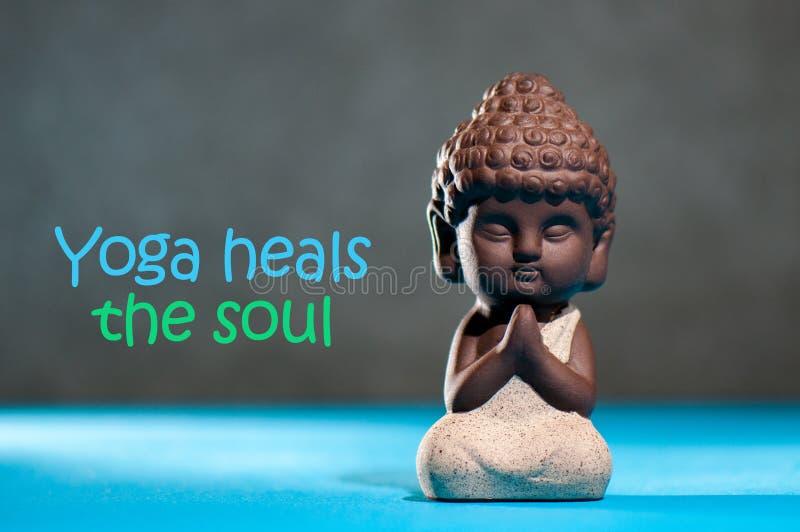 Yoga läker andan - den motivational inskriften på bild med behandla som ett barn buddha fotografering för bildbyråer