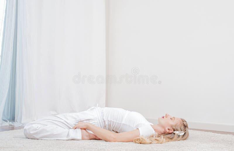 yoga La bella donna sta praticando l'yoga a casa, ragazza che fa la posa di Supta Virasanaexercise immagini stock