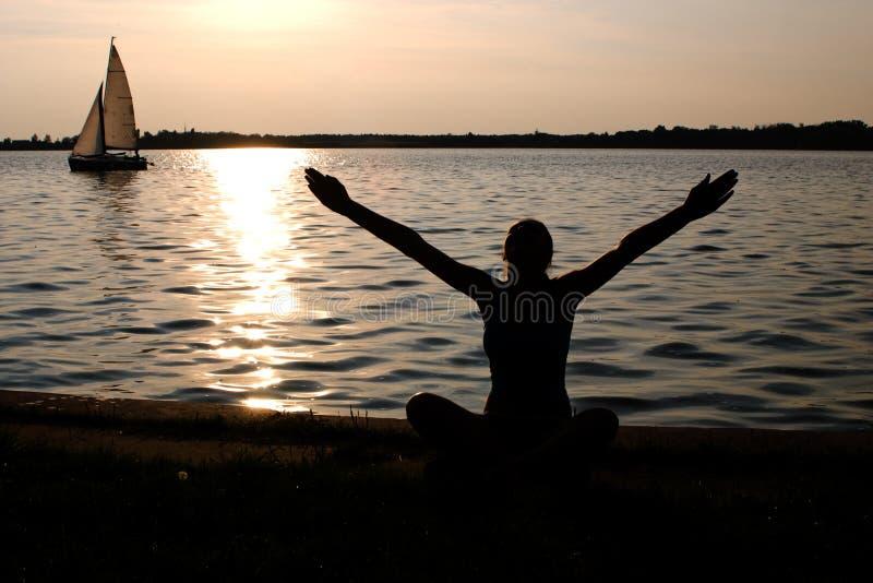 Yoga on the lake shore royalty free stock photo