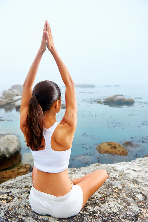Yoga lifestyle woman. Yoga beach woman doing pose at the ocean for zen health and peaceful lifestyle royalty free stock photos
