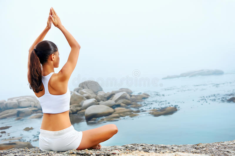 Yoga lifestyle woman. Yoga beach woman doing pose at the ocean for zen health and peaceful lifestyle stock photo