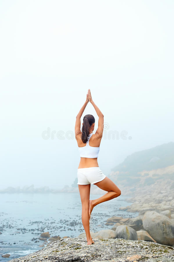Yoga lifestyle woman. Yoga beach woman doing pose at the ocean for zen health and peaceful lifestyle stock photos