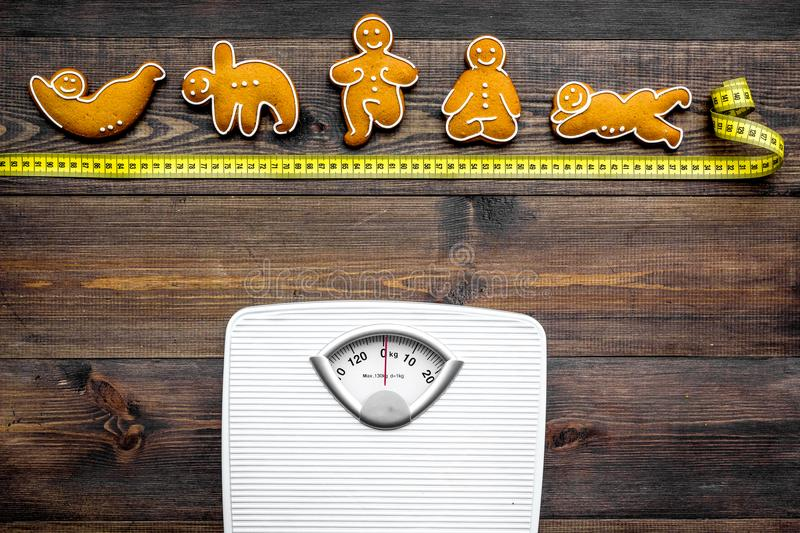 Yoga for lose weight. Scale, measuring tape and cookies in shape of yoga asans on dark wooden background top view stock image