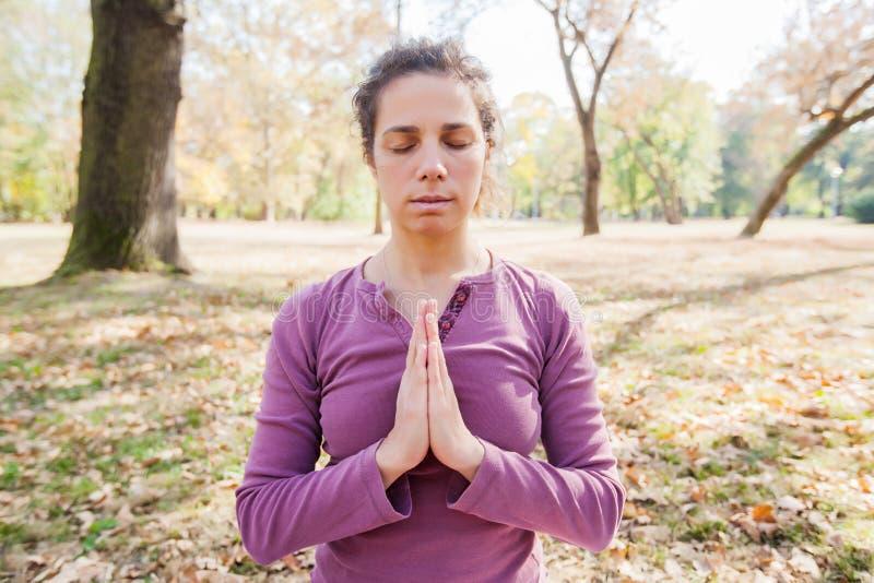 Yoga méditant et de pratique de jeune femme en bonne santé extérieur image libre de droits