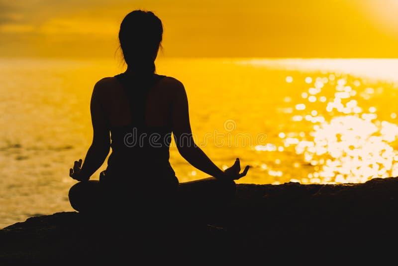 Yoga méditant et de pratique de silhouette de jeune femme sur le bea photographie stock