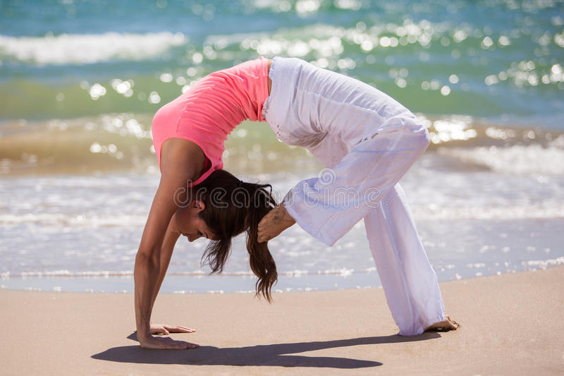 Yoga makes you flexible. Beautiful young woman holding a yoga pose at the beach stock photos