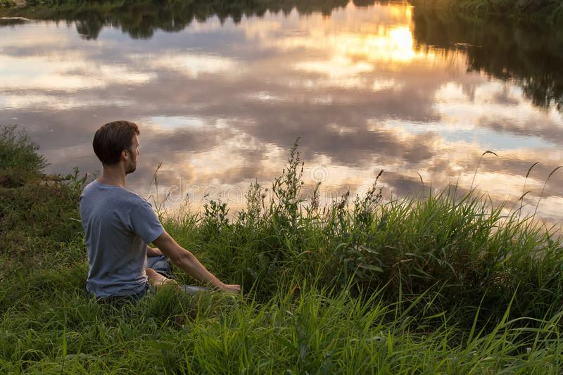 Yoga, man in lotus pose meditation, outdoors in nature, copy space royalty free stock photos