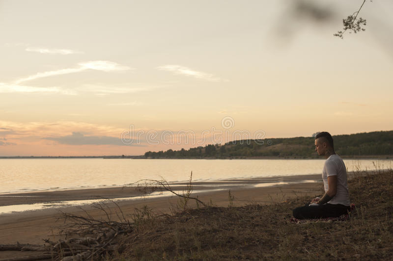 Man practising Yoga poses at the beach : Austockphoto in