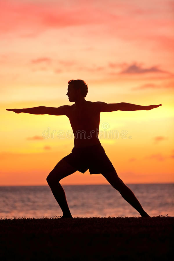 Yoga man training and meditating in warrior pose. Outside by beach at sunrise or sunset. Male yoga instructor working out training in serene ocean landscape royalty free stock images