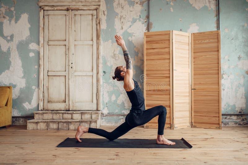 Yoga masculin avec le tatouage en main faisant l'exercice photographie stock libre de droits
