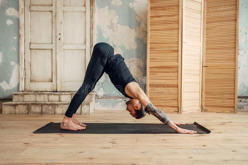 Yoga masculin faisant étirant l'exercice sur le tapis photo stock