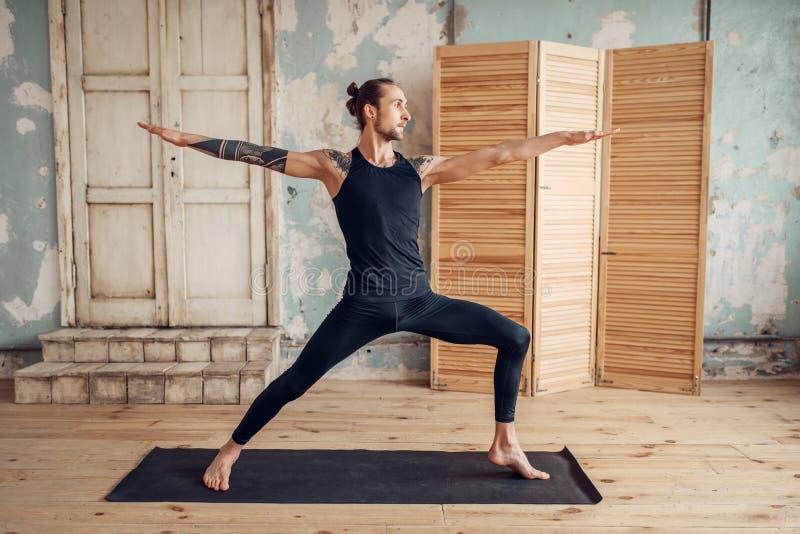 Yoga masculin faisant étirant l'exercice sur le tapis image stock