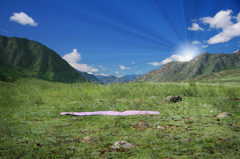 Download Yoga Mat On Green Field Near Mountains Stock Photo - Image: 15861658