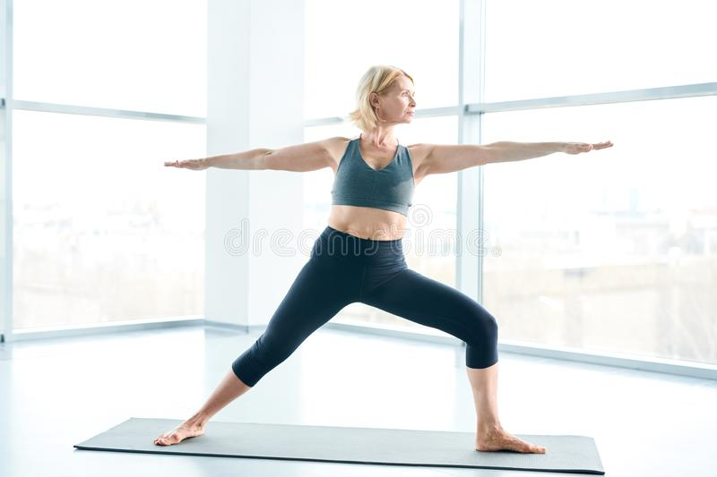 Yoga on mat. Middle-aged active blonde female in tracksuit standing on mat with outstretched legs and arms while practicing yoga stock images