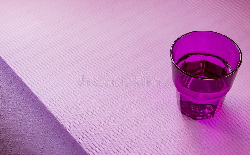 Yoga mat with purple glass of water.  royalty free stock photos