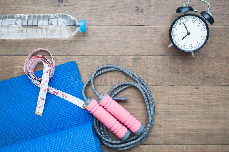 Yoga mat and sport equipment with measuring-tape, water and alarm clock on wood royalty free stock image