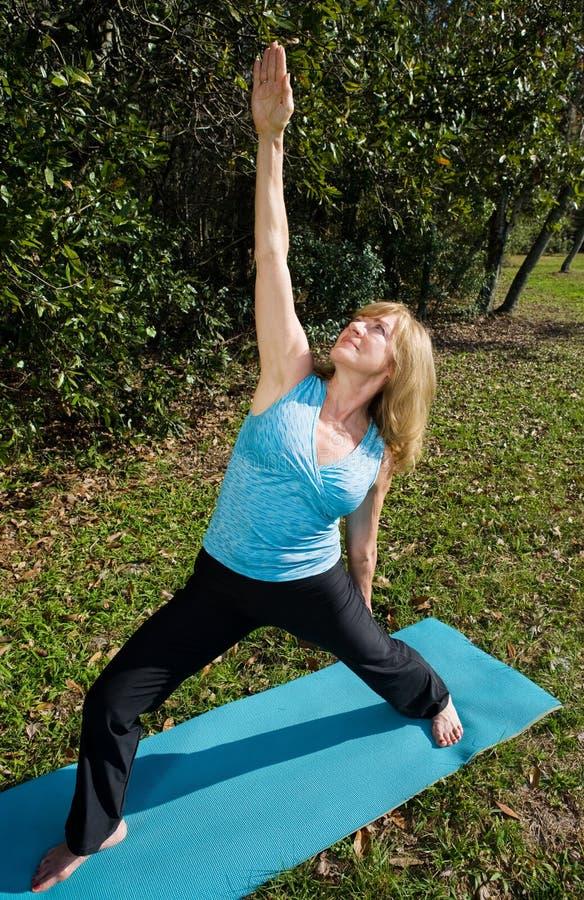 Yoga matura della donna - guerriero ascendente fotografie stock libere da diritti