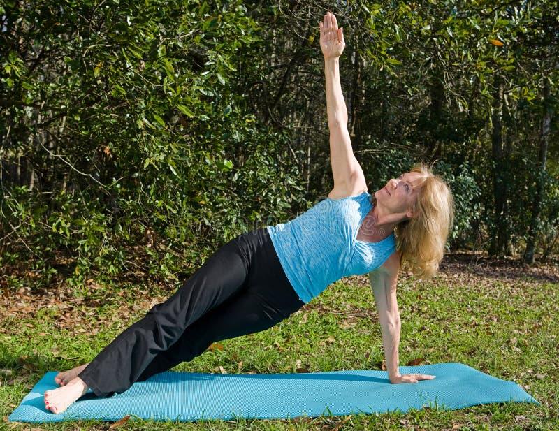 Yoga matura della donna - personale laterale Asana immagine stock