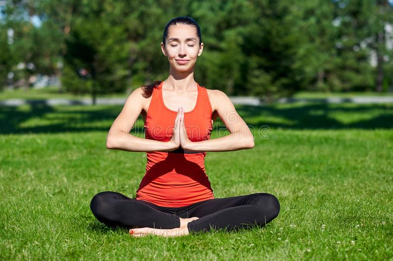 yoga Medita??o praticando da ioga da jovem mulher na natureza um parque Postura de Lotus Conceito do estilo de vida da sa?de imagem de stock