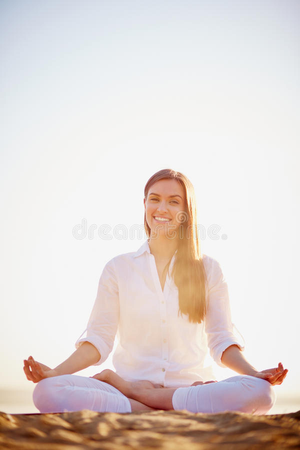 Yoga. Meditating woman looking at camera with smile stock photo