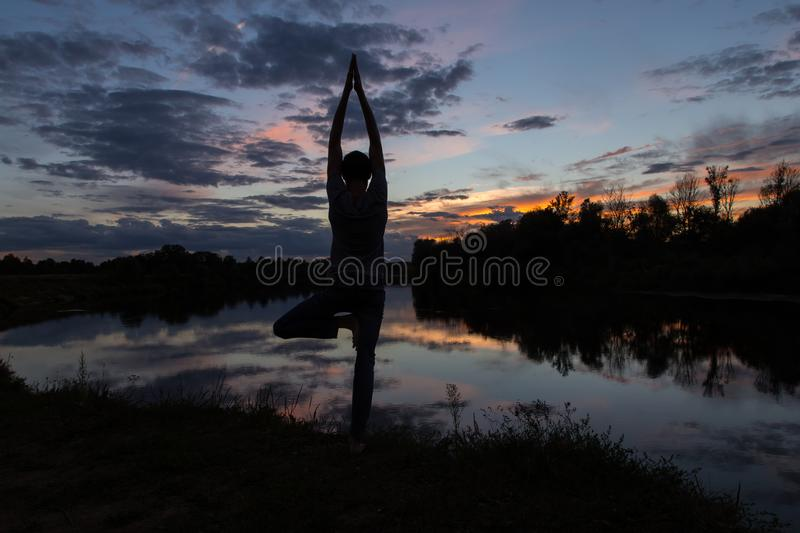 Yoga meditation concept, Man silhouette in sunset royalty free stock image