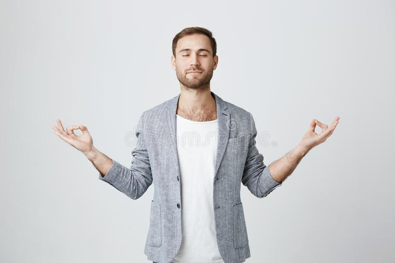 Yoga and meditation. Handsome man with beard dressed in jacket keeping eyes closed while meditating, feeling relaxed. Yoga and meditation. Handsome stylish man stock image