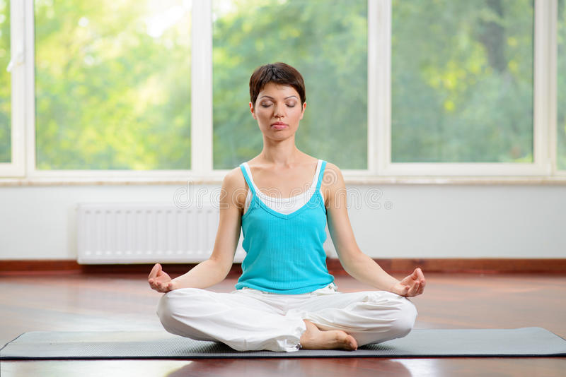 Yoga and Meditation Indoors. Young Woman Sitting on Lotus Position and Meditating with Eyes Closed. Yoga and Meditation Indoors. Young Calm Woman Sitting on royalty free stock images