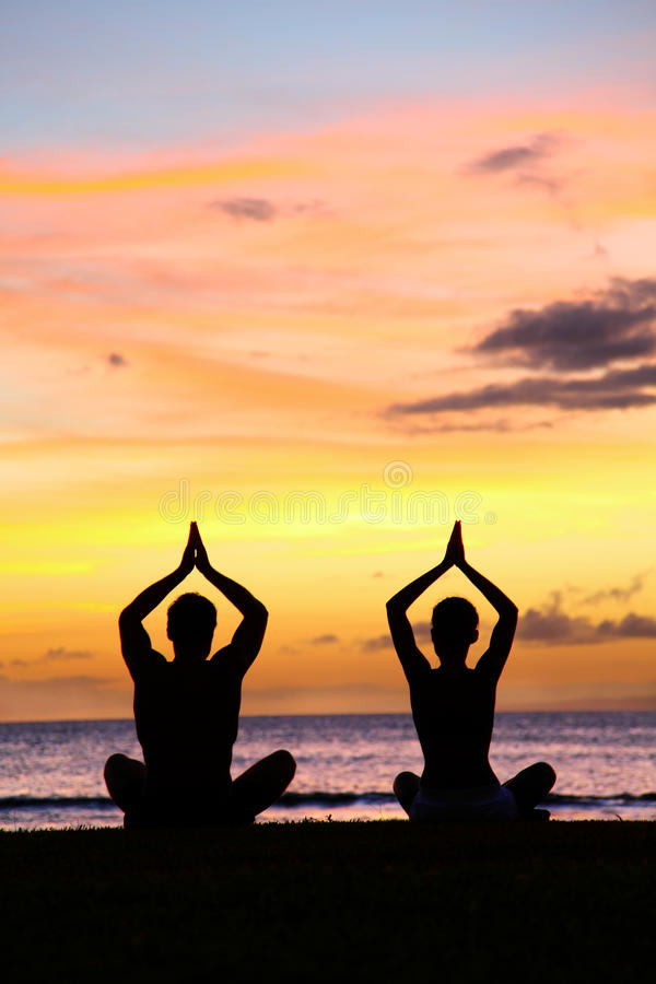 Yoga meditation - silhouettes of people at sunset. Silhouette of a couple practicing yoga at sunset sitting on a beach in the lotus position with their hands royalty free stock images