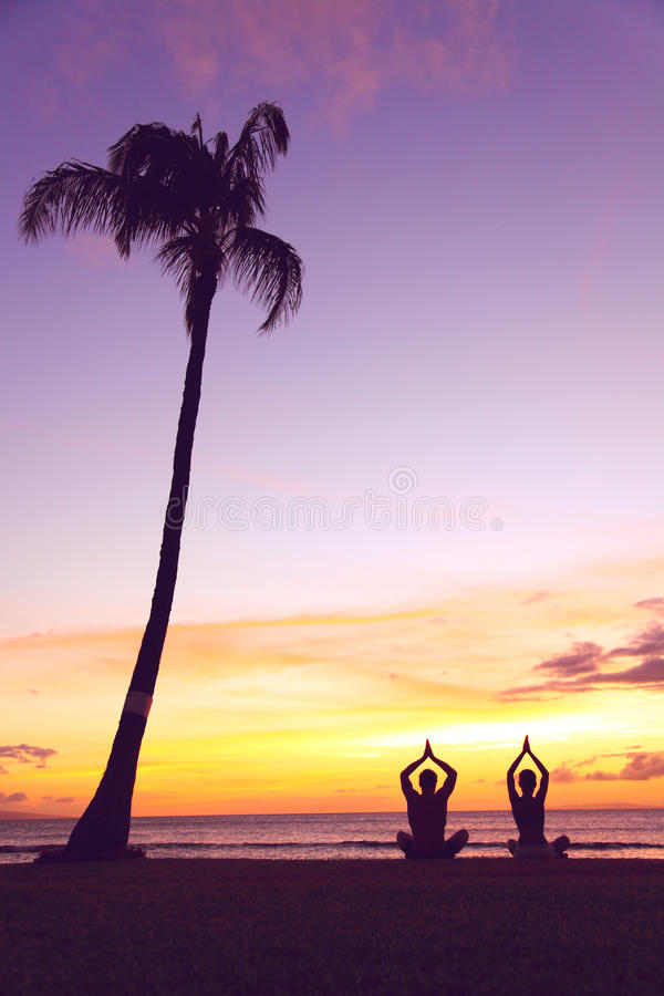 Yoga meditation - silhouettes of people at sunset. Silhouette of a couple practising yoga at sunset sitting on a beach in the lotus position with their hands stock images