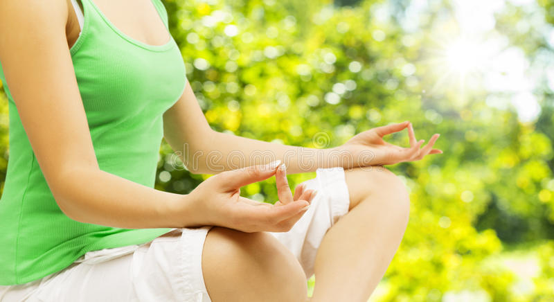Yoga Meditation, Sitting Outdoors in Lotus Pose, Woman Meditating Hand over Green Unfocused Park stock photography