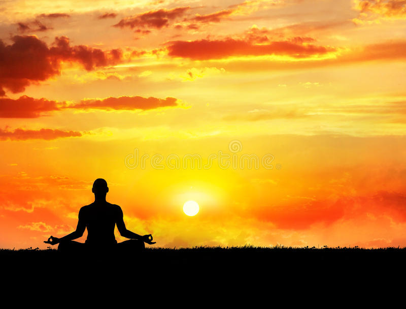 Yoga meditation at sunset. Yoga meditation in lotus pose by man silhouette at sunset sky background. Free space for text and can be used as template for web-site royalty free stock photo