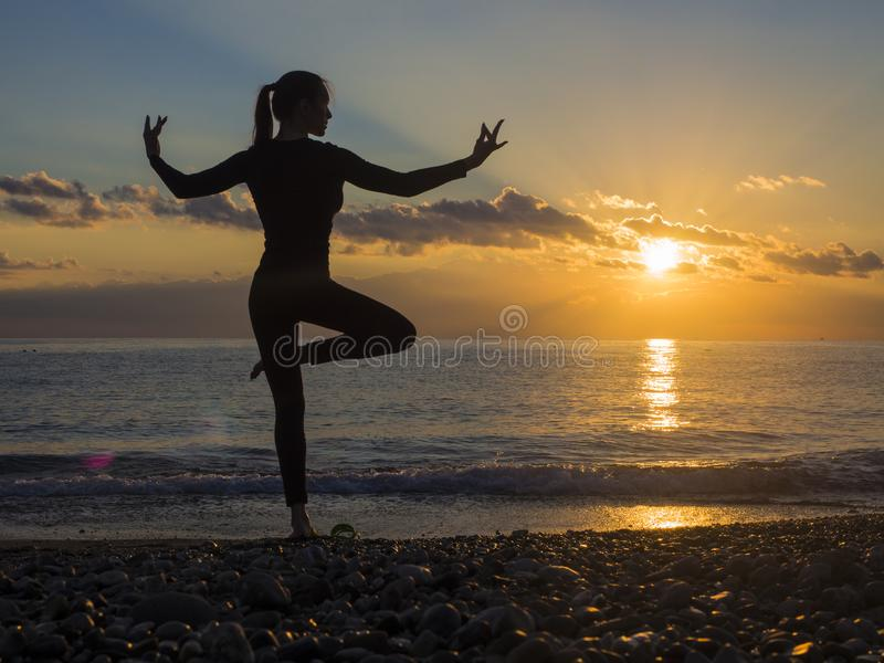 Yoga meditation woman silhouette on the ocean during amazing sunset. Healthy lifestyle. royalty free stock image