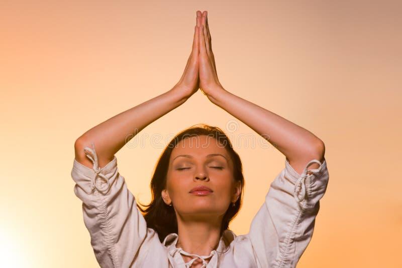 Yoga mot den orange himlen royaltyfri fotografi