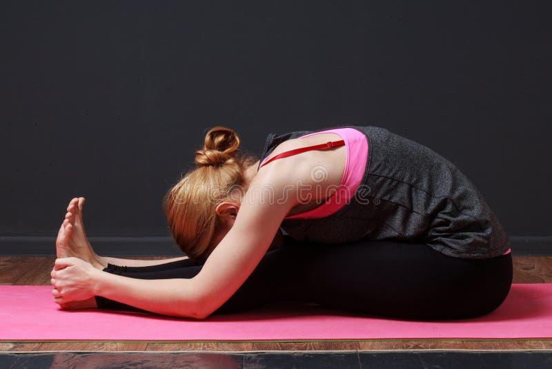 Yoga Mujer rubia joven que hace ejercicio de la yoga fotografía de archivo