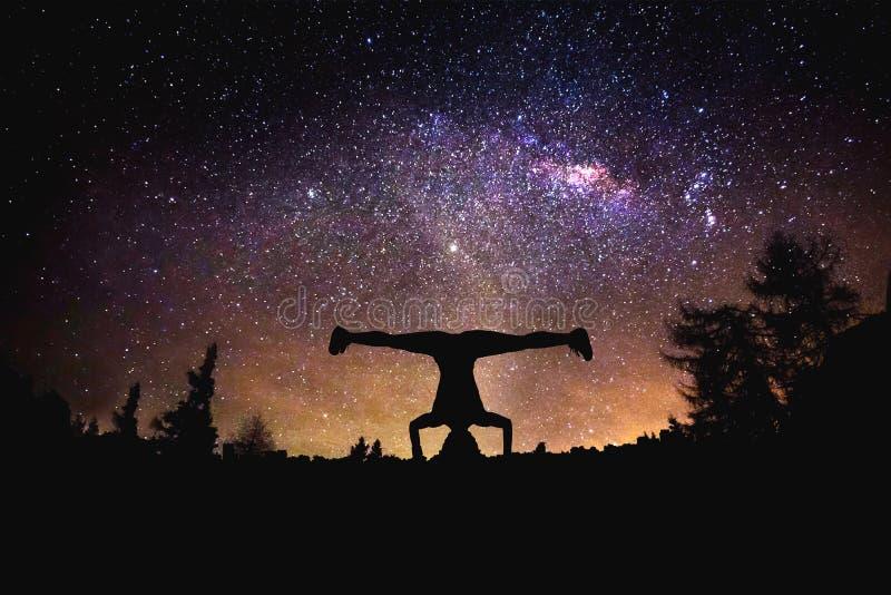 Yoga am Nachtsternenklaren Himmelhintergrund Gemischte Medien stockfotos
