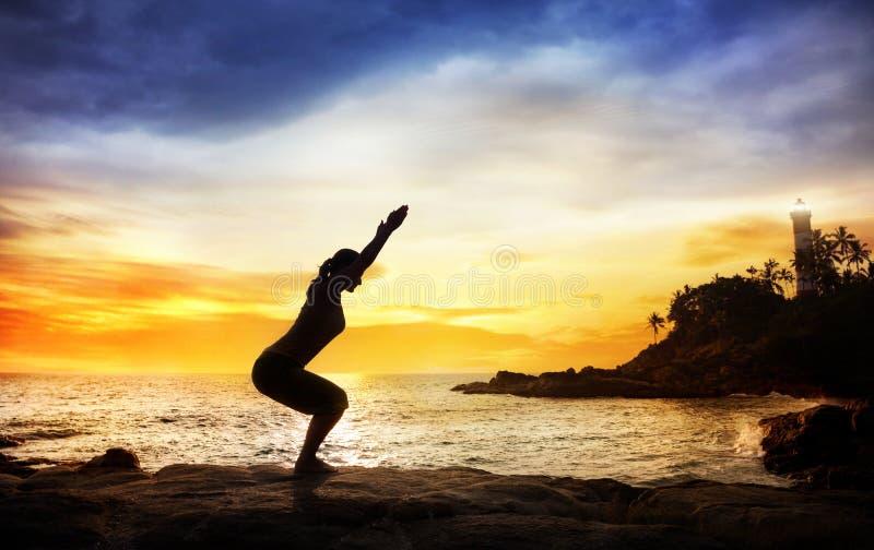 Yoga nahe Leuchtturm stockbild