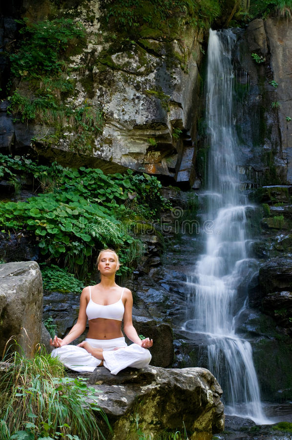 Yoga in the nature. Beautiful young woman meditating in lotus position while doing yoga in the nature near waterfall