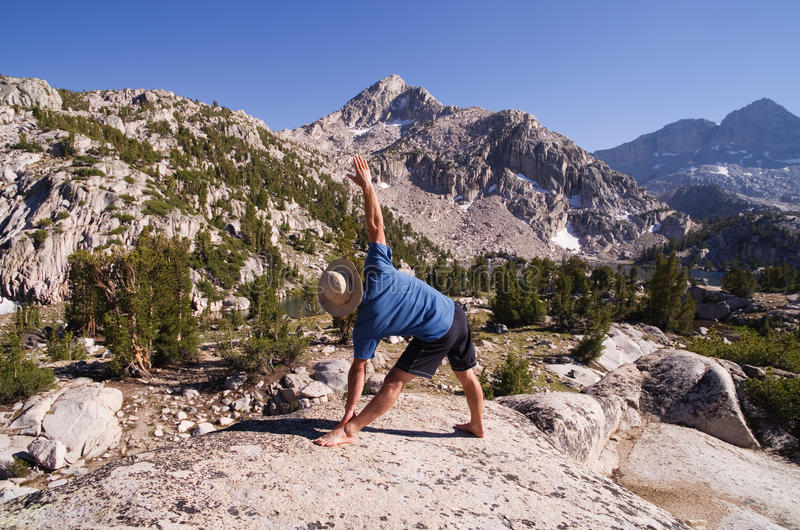 Yoga in nature. A man does the yoga triangle pose or trikanasana in nature stock photos