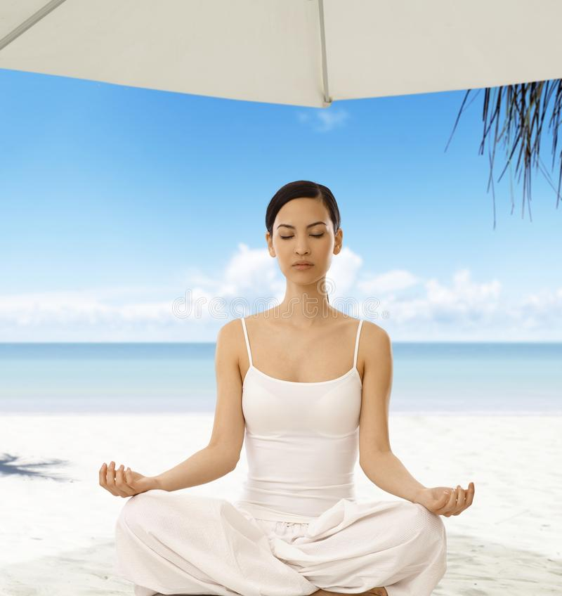 Yoga in nature. Beautiful woman practicing yoga on the beach, sitting eyes closed, meditating, relaxing stock images