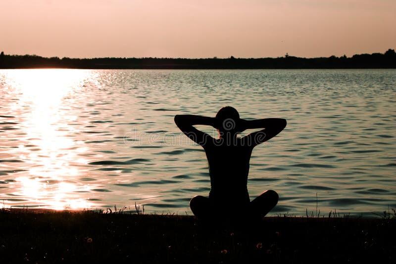 Yoga op de meerkust stock afbeelding