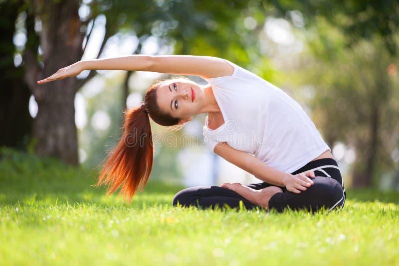 Yoga openlucht De gelukkige vrouw die yogaoefeningen doen, mediteert stock foto